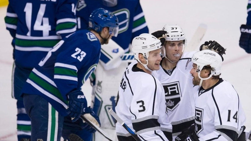 Los Angeles Kings right wing Justin Williams (14) celebrates his goal with teammates Nick Shore (37) and Brayden McNabb (3) during the second period of an NHL hockey game against the Vancouver Canucks on Thursday, March 12, 2015, in Vancouver, British Columbia. (AP Photo/The Canadian Press, Jonathan Hayward)