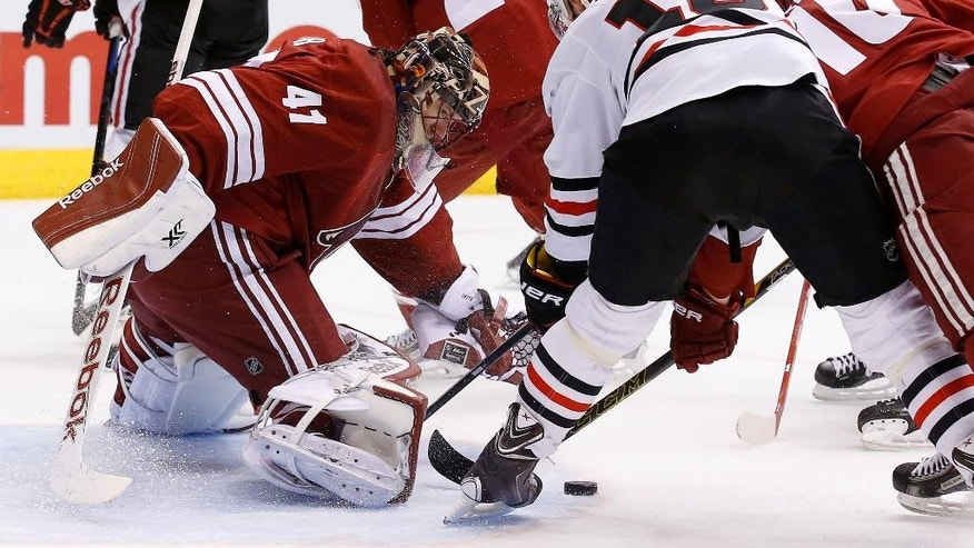Chicago Blackhawks' Jonathan Toews (19) tries to get a shot off in front of Arizona Coyotes' Mike Smith (41) as Coyotes' Martin Erat (10), of the Czech Republic, defends during the first period of an NHL hockey game Thursday, March 12, 2015, in Glendale, Ariz. (AP Photo/Ross D. Franklin)