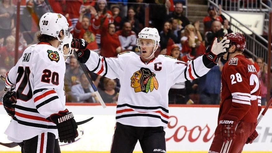 Chicago Blackhawks' Jonathan Toews (19) celebrates a goal by teammate Andrew Shaw with Brandon Saad (20) as Arizona Coyotes' Lauri Korpikoski (28), of Finland, skates past during the first period of an NHL hockey game Thursday, March 12, 2015, in Glendale, Ariz. (AP Photo/Ross D. Franklin)
