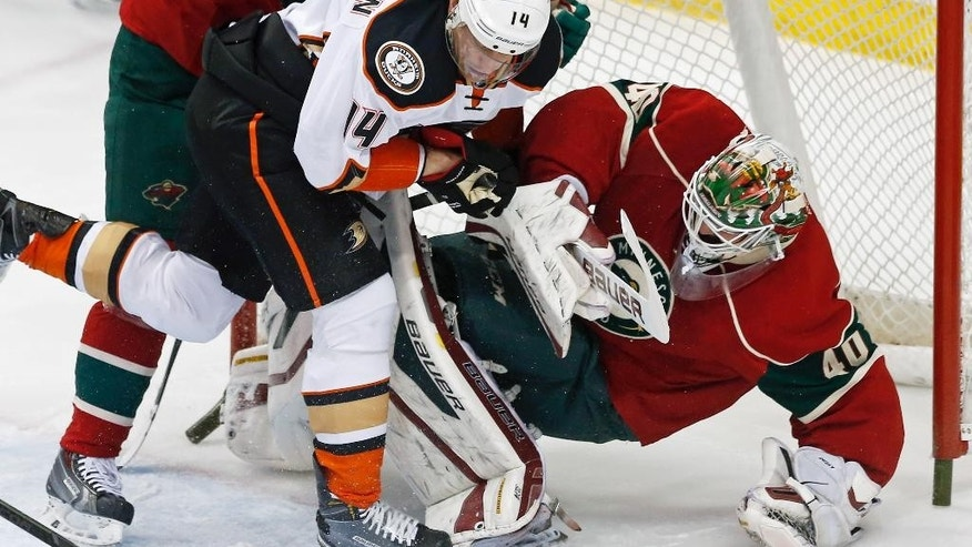 Minnesota Wild goalie Devan Dubnyk, right, is upended by Anaheim Ducks' Tomas Fleischmann, of the Czech Republic, in the first period of an NHL hockey game, Friday, March 13, 2015, in St. Paul, Minn. Fleischmann received a two-minute penalty for goaltender interference. (AP Photo/Jim Mone)