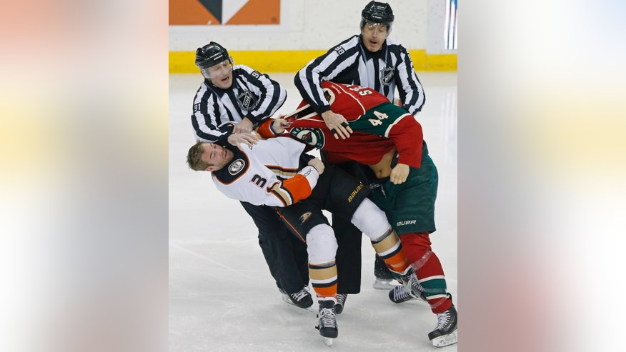 Referees Don Henderson, left, and Mike Cvik break up a fight between Anaheim Ducks' Clayton Stoner, left, and Minnesota Wild's Chris Stewart in the first period of an NHL hockey game Friday, March 13, 2015, in St. Paul, Minn. (AP Photo/Jim Mone)