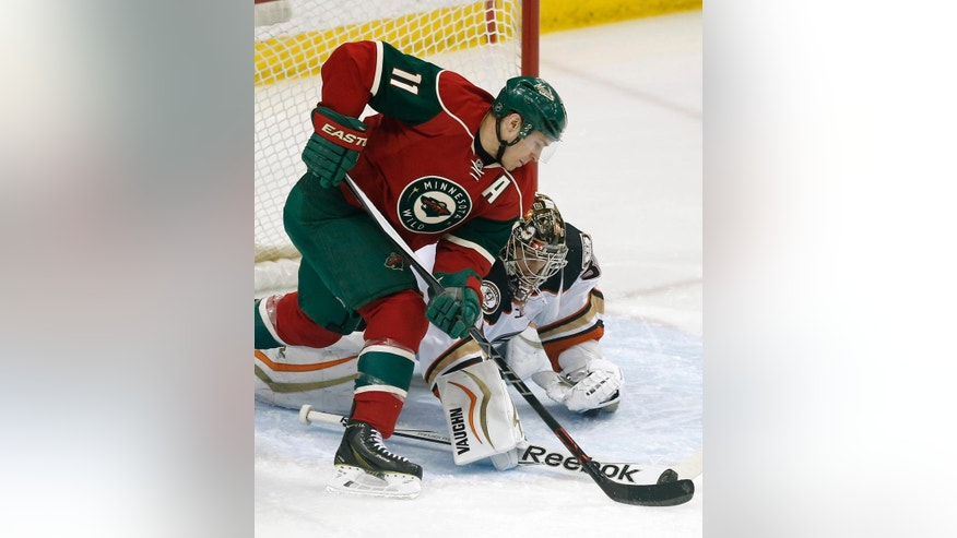 Minnesota Wild's Zach Parise, left, shoots against Anaheim Ducks goalie John Gibson in the first period of an NHL hockey game Friday, March 13, 2015, in St. Paul, Minn. (AP Photo/Jim Mone)