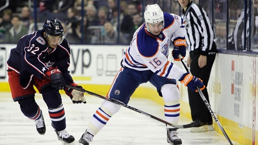 Edmonton Oilers' Teddy Purcell, right, moves with the puck as Columbus Blue Jackets' Adam Cracknell defends during the first period of an NHL hockey game Friday, March 13, 2015, in Columbus, Ohio. (AP Photo/Jay LaPrete)