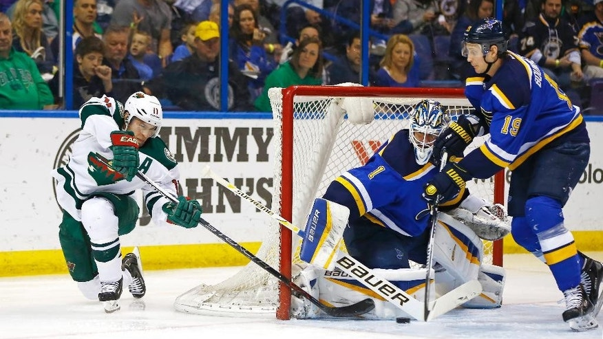 Minnesota Wild's Zach Parise, left, takes a shot on goal as St. Louis Blues goalie Brian Elliott and Jay Bouwmeester, right, defend the net during the second period of an NHL hockey game Saturday, March 14, 2015, in St. Louis.  (AP Photo/Billy Hurst)