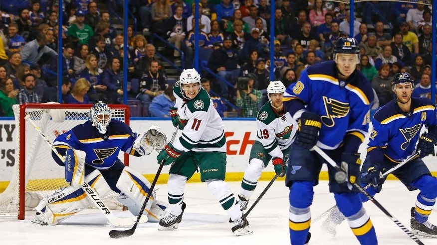 St. Louis Blues goalie Brian Elliott keeps his eye on the puck as Minnesota Wild's Zach Parise attempts to screen during the second period of an NHL hockey game Saturday, March 14, 2015, in St. Louis.  (AP Photo/Billy Hurst)