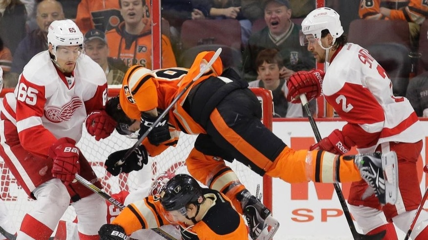 Philadelphia Flyers' Jakub Voracek (93), of the Czech Republic, leaps over Brayden Schenn (10) as they battle for the puck with Detroit Red Wings' Brendan Smith (2) and Danny DeKeyser (65) during the third period of an NHL hockey game, Saturday, March 14, 2015, in Philadelphia. Philadelphia won 7-2. (AP Photo/Matt Slocum)