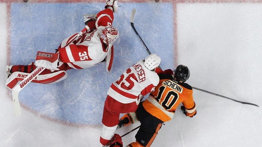 Philadelphia Flyers' Brayden Schenn (10) scores a goal past Detroit Red Wings' Jimmy Howard (35) as Danny DeKeyser (65) tries to defend during the second period of an NHL hockey game, Saturday, March 14, 2015, in Philadelphia. (AP Photo/Matt Slocum)