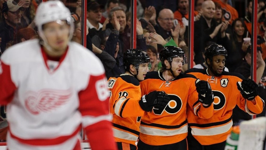 Philadelphia Flyers' Wayne Simmonds, from right, Jakub Voracek, of the Czech Republic, and Brayden Schenn celebrate after Schenn's goal as Detroit Red Wings' Danny DeKeyser skates by during the second period of an NHL hockey game, Saturday, March 14, 2015, in Philadelphia. (AP Photo/Matt Slocum)