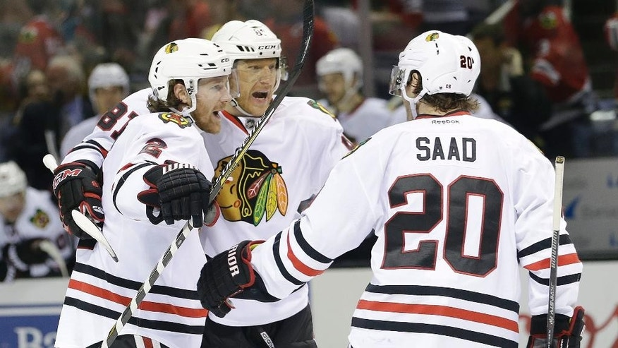 Chicago Blackhawks' Duncan Keith, left, celebrates his goal with teammates Marian Hossa, center, and Brandon Saad (20) during the second period of an NHL hockey game against the San Jose Sharks, Saturday, March 14, 2015, in San Jose, Calif. (AP Photo/Marcio Jose Sanchez)