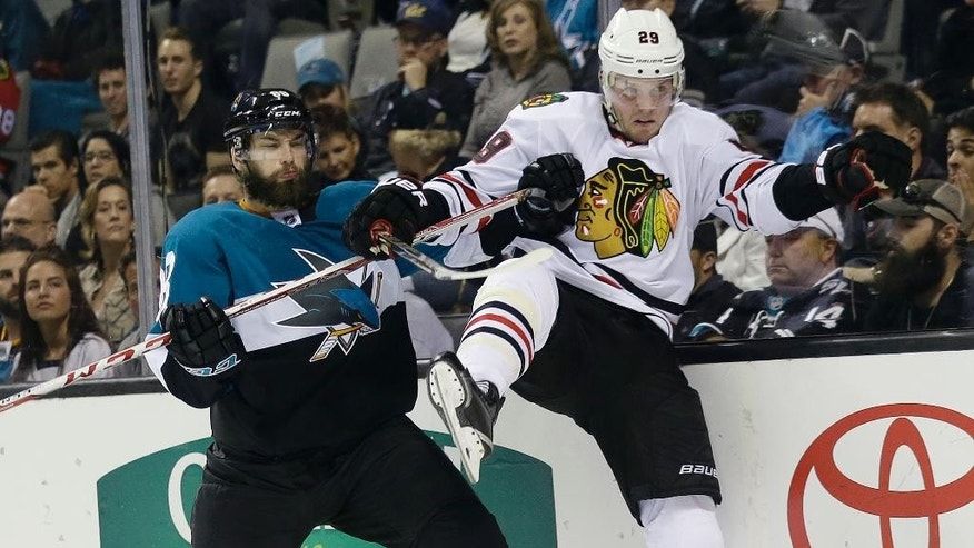 Chicago Blackhawks' Bryan Bickell (29) collides against the boards with San Jose Sharks' Brent Burns during the second period of an NHL hockey game Saturday, March 14, 2015, in San Jose, Calif. (AP Photo/Marcio Jose Sanchez)