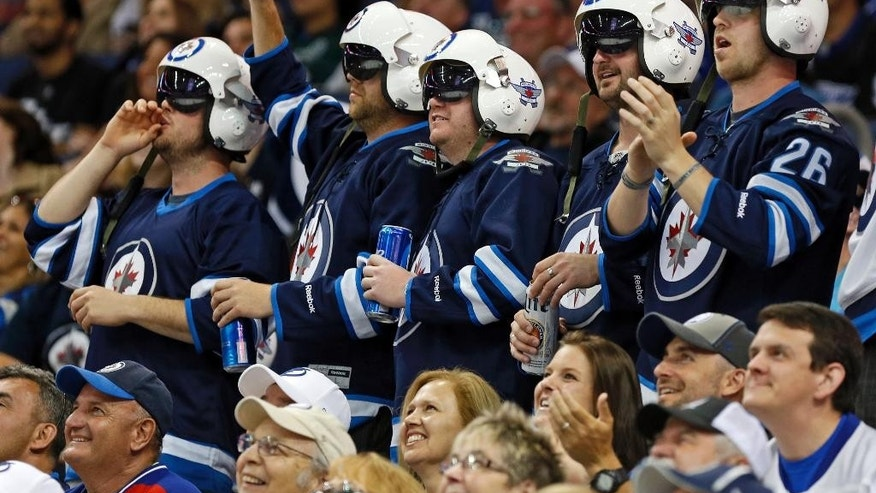 A group of Winnipeg Jets fans cheer on their team during the second period of an NHL hockey game against the Tampa Bay Lightning Saturday, March 14, 2015, in Tampa, Fla. (AP Photo/Mike Carlson)