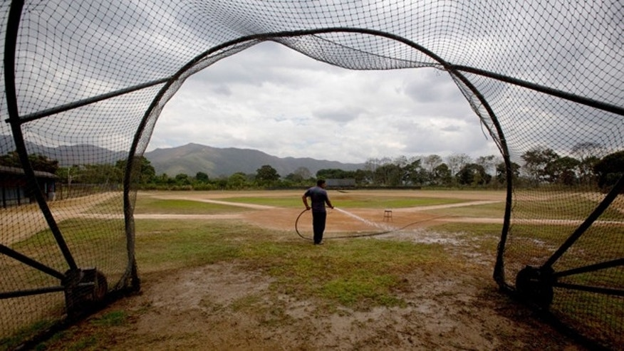 In this March 10, 2015 photo, Seattle Mariners ground worker Carlos Galindez sprays water on the field after a training session at the Seattle Mariners' baseball academy in Aguirre, Venezuela. The teamâs operations are coming to an abrupt end and moving to Dominican Republic, the latest in a string of American teams that have abandoned Venezuela in the past decade as a result of economic turmoil, rampant crime and mounting tensions with the United States. âI donât know why theyâre going,â said Galindez, holding back tears as he reflected proudly on his work caring for the academyâs two baseball diamonds. âAll I can say is they treated us well.â (AP Photo/Fernando Llano)