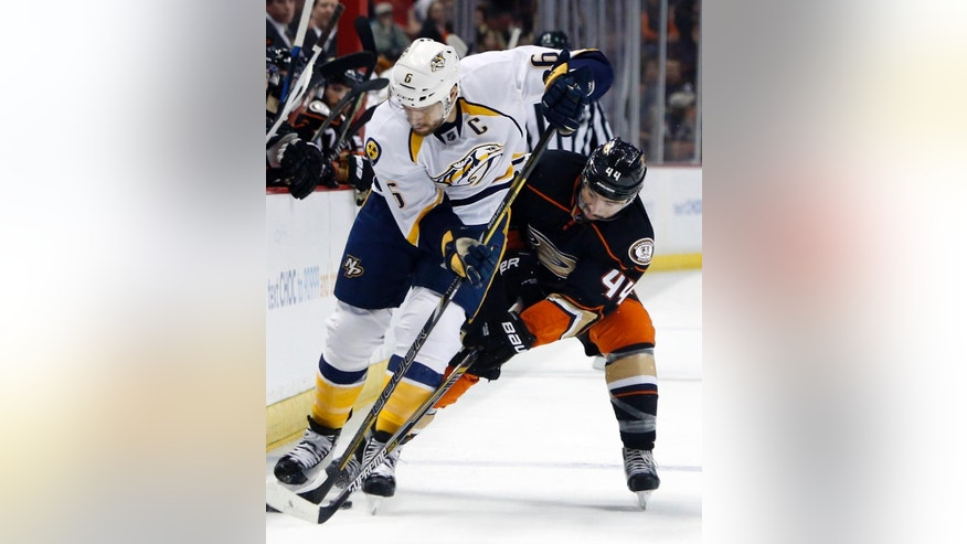 Nashville Predators'  Shea Weber, left, and Anaheim Ducks' Nate Thompson fight for the puck in the first period of an NHL hockey game  in Anaheim, Calif., Sunday, March 15, 2015. (AP Photo/Christine Cotter)