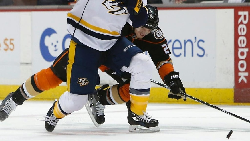 Nashville Predators' Colin Wilson (33) battles Anaheim Ducks' Simon Despres (24) in the first period of an NHL hockey game in Anaheim, Calif., Sunday, March 15, 2015. (AP Photo/Christine Cotter)