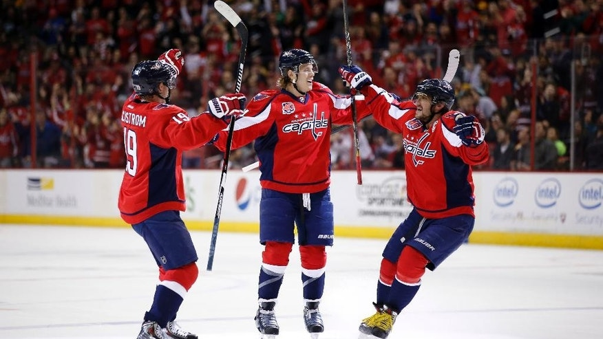 Washington Capitals center Nicklas Backstrom (19), from Sweden, defenseman John Carlson (74) and left wing Alex Ovechkin (8), from Russia, celebrate Carlson's goal in the first period of an NHL hockey game against the Boston Bruins, Sunday, March 15, 2015, in Washington. Backstrom was given an assist on the goal and with that became the Capitals franchise all time assist leader. (AP Photo/Alex Brandon)