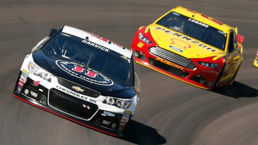 Kevin Harvick (4) leads Joey Logano in the 65th lap during a NASCAR Sprint Cup Series auto race on Sunday, March 15, 2015, in Avondale, Ariz. (AP Photo/Rick Scuteri)