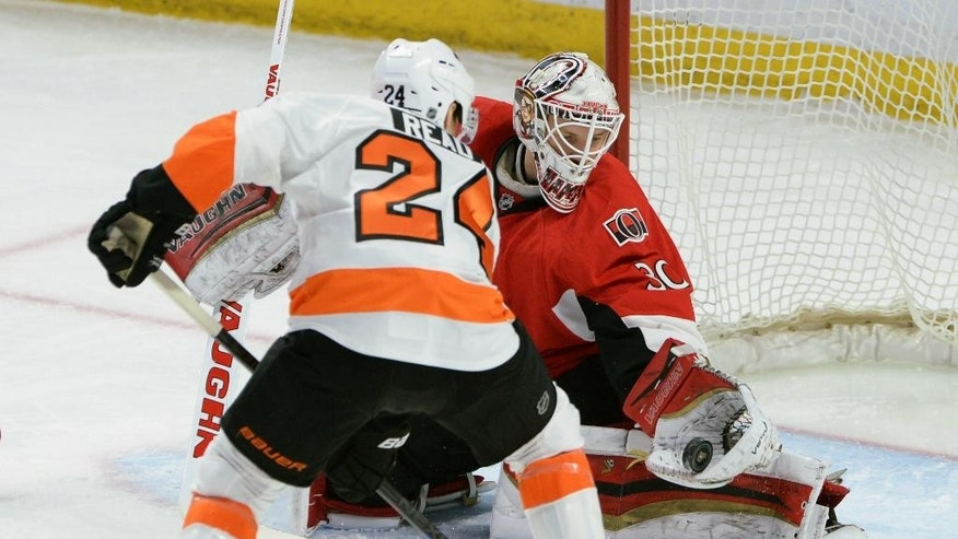 Ottawa Senators' goalie Andrew Hammond makes a glove save on a shot from Philadelphia Flyers' Matt Read during first period NHL hockey action in Ottawa, Ontario, Sunday, March 15, 2015. (AP Photo/The Canadian Press, Sean Kilpatrick)