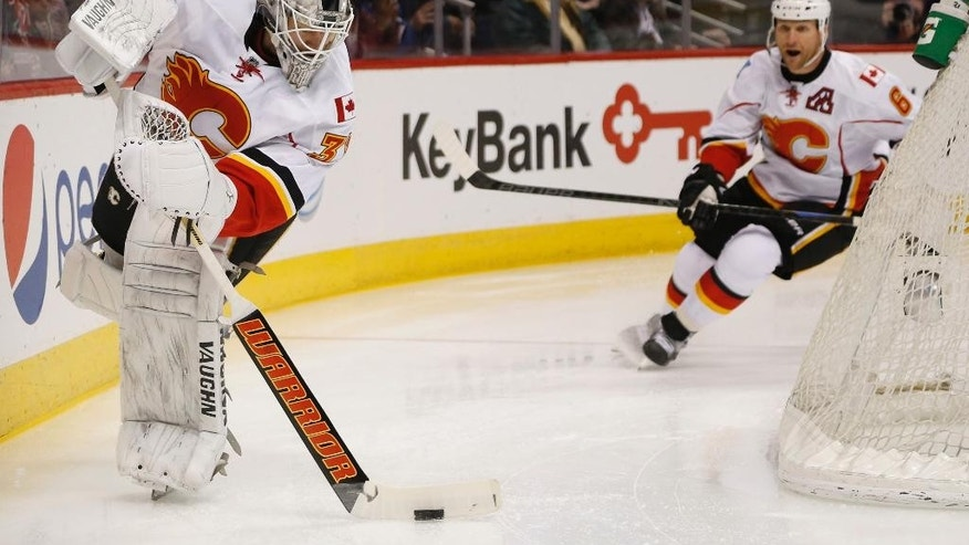 Calgary Flames goalie Karri Ramo, front, of Finland, clears the puck as defenseman Dennis Wideman approaches, during the first period of an NHL hockey game against the Colorado Avalanche on Saturday, March 14, 2015, in Denver. (AP Photo/David Zalubowski)