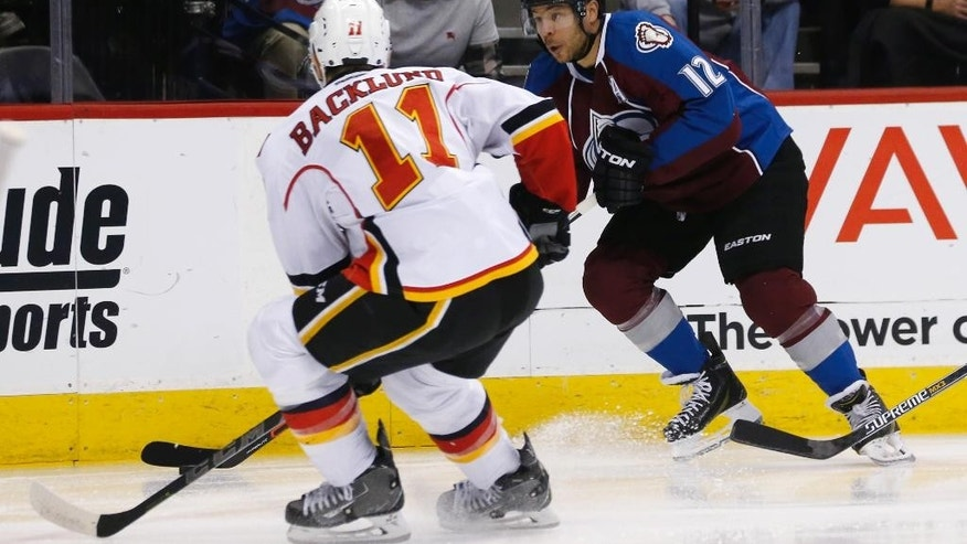 Colorado Avalanche right wing Jarome Iginla, back, races along the boards with the puck as Calgary Flames center Mikael Backlund, of Sweden, defends duringthe first period of an NHL hockey game Saturday, March 14, 2015, in Denver. (AP Photo/David Zalubowski)