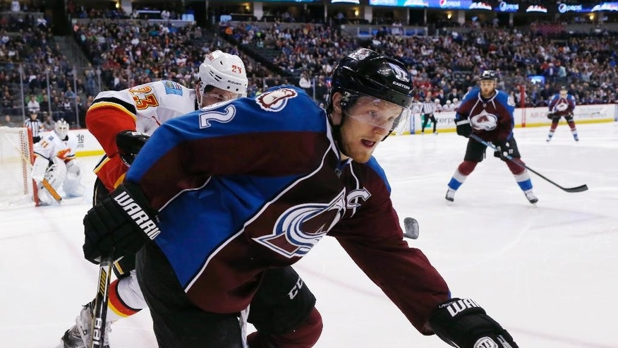 Colorado Avalanche left wing Gabriel Landeskog, front, of Sweden, pursues the puck into the corner with Calgary Flames center Sean Monahan during the first period of an NHL hockey game Saturday, March 14, 2015, in Denver. (AP Photo/David Zalubowski)