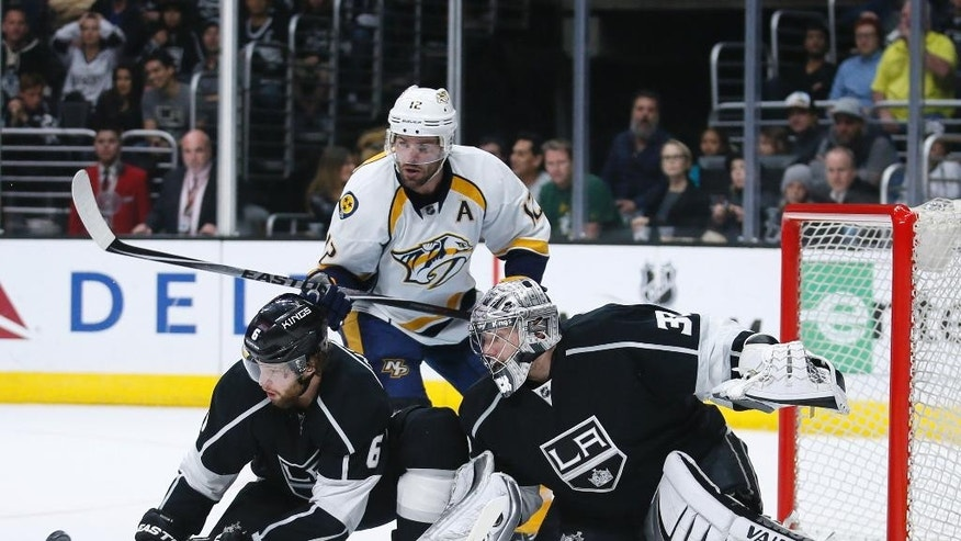 Los Angeles Kings defenseman Jake Muzzin, left, helps goalie Jonathan Quick, right, prevent a goal while Nashville Predators center Mike Fisher, rear, looks for the puck during the first period of an NHL hockey game Saturday, March 14, 2015, in Los Angeles. (AP Photo/Danny Moloshok)
