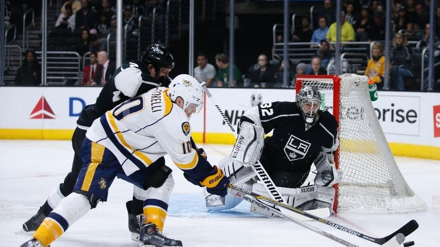 Nashville Predators center Mike Santorelli attempts a shot while Los Angeles Kings defenseman Matt Greene, back, and goalie Jonathan Quick, right, defend during the first period of an NHL hockey game Saturday, March 14, 2015, in Los Angeles. (AP Photo/Danny Moloshok)