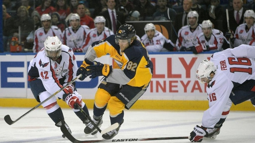 Washington Capitals' Joel Ward (42) and Eric Fehr (16) battle for the puck with Buffalo Sabres' Marcus Foligno (92) during the first period of an NHL hockey game Monday, March 16, 2015, in Buffalo, N.Y. (AP Photo/Gary Wiepert)