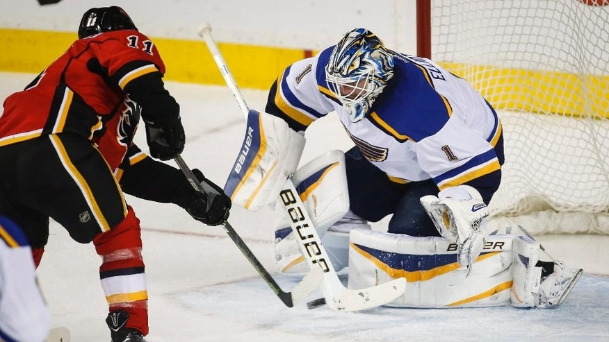 St. Louis Blues goalie Brian Elliott, right, blocks a shot from Calgary Flames' Mikael Backlund, from Sweden, during the second period of an NHL hockey game, Tuesday, March 17, 2015 in Calgary, Alberta. (AP Photo/Canadian Press, Jeff McIntosh)