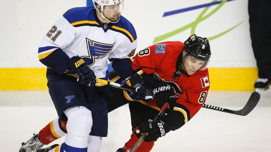 St. Louis Blues' Patrik Berglund, left, from Sweden, checks Calgary Flames' Joe Colborne during the second period of an NHL hockey game, Tuesday, March 17, 2015 in Calgary, Alberta. (AP Photo/Canadian Press, Jeff McIntosh)