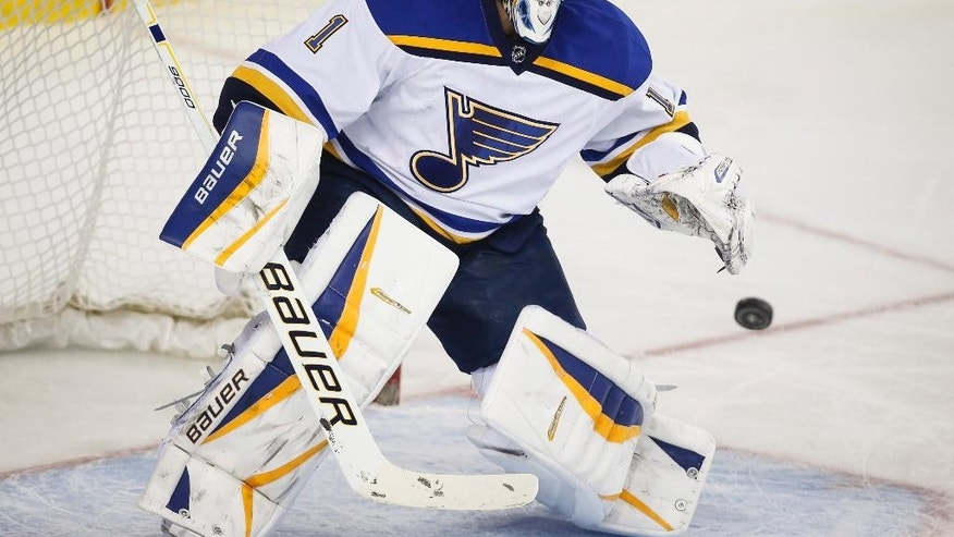 St. Louis Blues goalie Brian Elliott deflects the puck during the first period of an NHL hockey game, Tuesday, March 17, 2015 in Calgary, Alberta. (AP Photo/Canadian Press, Jeff McIntosh)