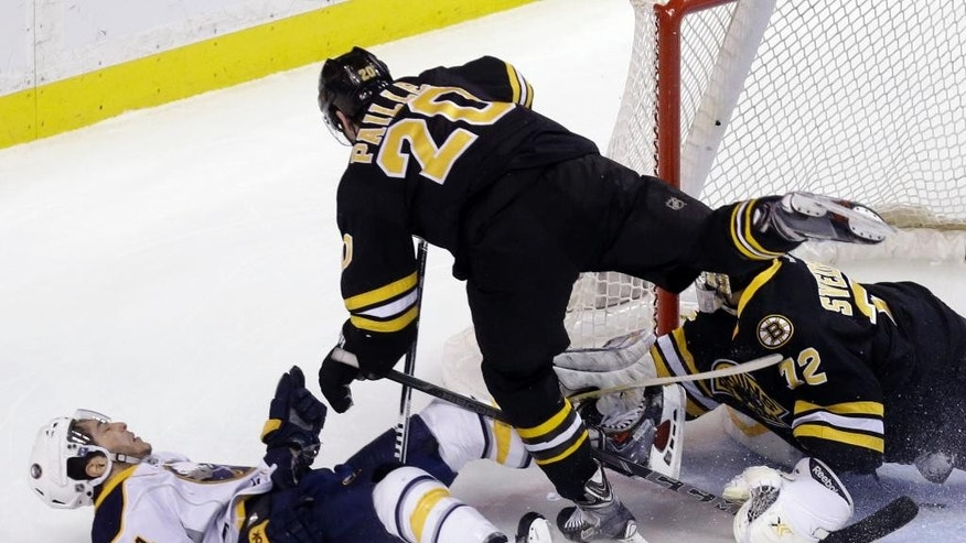 Boston Bruins left wing Daniel Paille (20) checks Buffalo Sabres center Phil Varone (84) to the ice as he helps Boston Bruins goalie Niklas Svedberg (72) protect the net from an attempt during the first period of an NHL hockey game in Boston, Tuesday, March 17, 2015. (AP Photo/Elise Amendola)