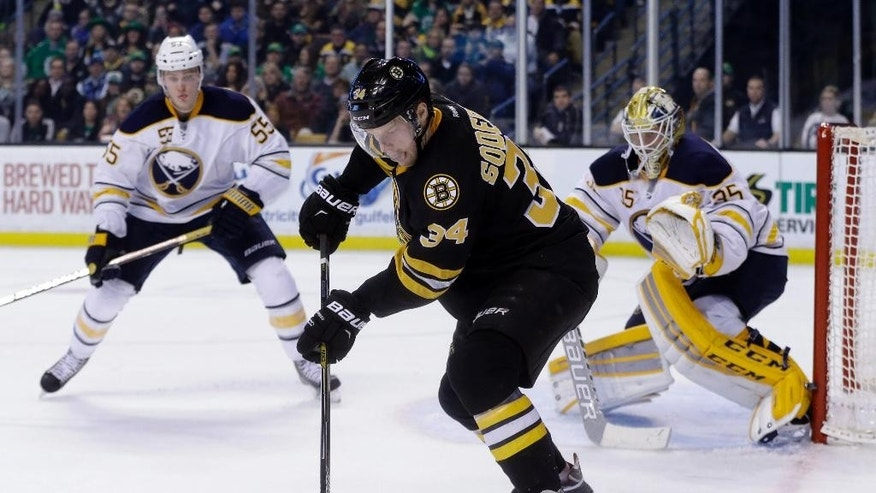 Boston Bruins center Carl Soderberg (34) handles the puck as Buffalo Sabres goalie Anders Lindback (35) and defenseman Rasmus Ristolainen (55) guard the net during the second period of an NHL hockey game in Boston, Tuesday, March 17, 2015. (AP Photo/Elise Amendola)
