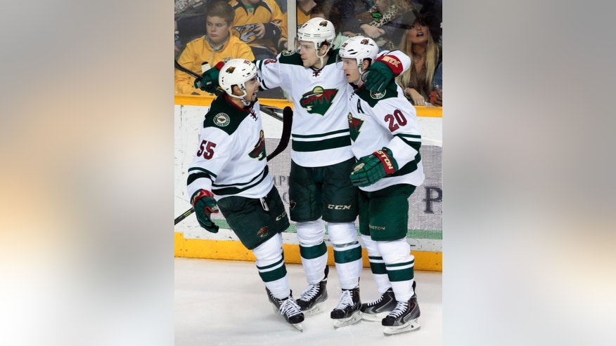 Minnesota Wild center Charlie Coyle (3) is congratulated by Matt Dumba (55) and Ryan Suter (20) after Coyle scored his second goal of the game against the Nashville Predators in the third period of an NHL hockey game Tuesday, March 17, 2015, in Nashville, Tenn. The Wild won in overtime 3-2. (AP Photo/Mark Humphrey)