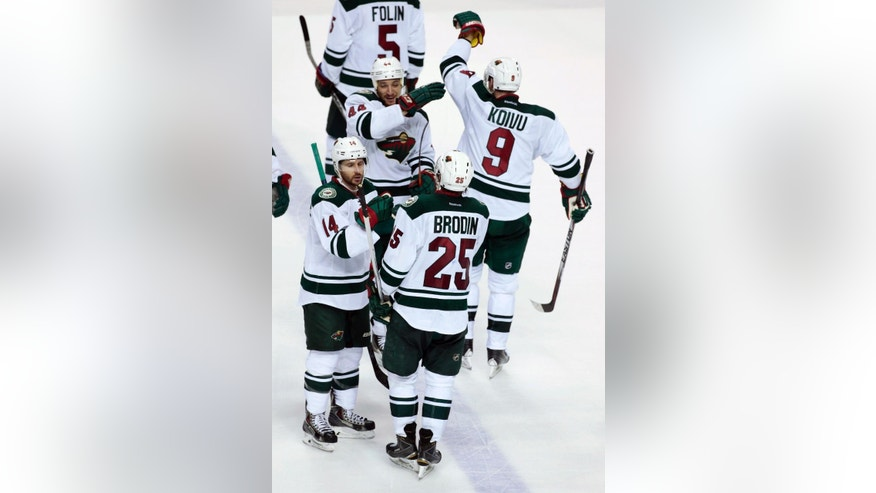 Minnesota Wild players celebrate after beating the Nashville Predators in overtime at an NHL hockey game Tuesday, March 17, 2015, in Nashville, Tenn. The Wild won 3-2. (AP Photo/Mark Humphrey)
