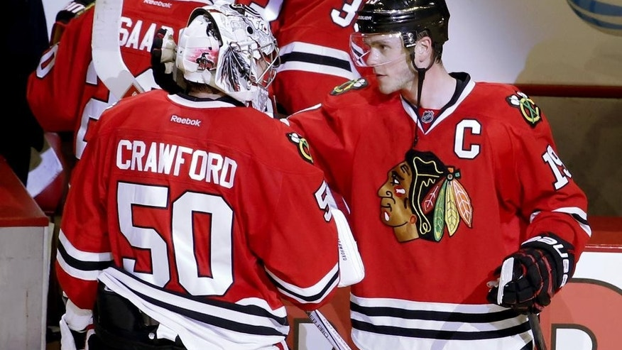 Chicago Blackhawks center Jonathan Toews (19) celebrates the Blackhawks' 4-1 win over the New York Islanders with goalie Corey Crawford (50) after an NHL hockey game Tuesday, March 17, 2015, in Chicago. (AP Photo/Charles Rex Arbogast)