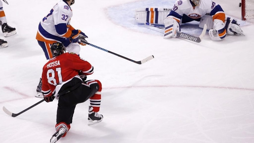 Chicago Blackhawks right wing Marian Hossa (81) watches his shot score on New York Islanders goalie Michal Neuvirth (30) and Islanders Brian Strait  watch during the second period of an NHL hockey game Tuesday, March 17, 2015, in Chicago. (AP Photo/Charles Rex Arbogast)