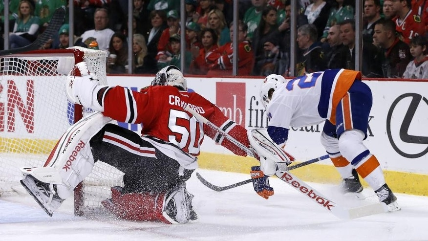 Chicago Blackhawks goalie Corey Crawford (50) spins around the net after a minor collision with New York Islanders center Anders Lee (27) during the first period of an NHL hockey game Tuesday, March 17, 2015, in Chicago. (AP Photo/Charles Rex Arbogast)
