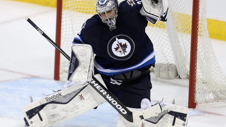 Winnipeg Jets goaltender Ondrej Pavelec (31) makes a high glove save on San Jose Sharks' Barclay Goodrow (89) during third period NHL hockey action in Winnipeg, Manitoba, Tuesday, March 17, 2015. (AP Photo/The Canadian Press, Trevor Hagan)