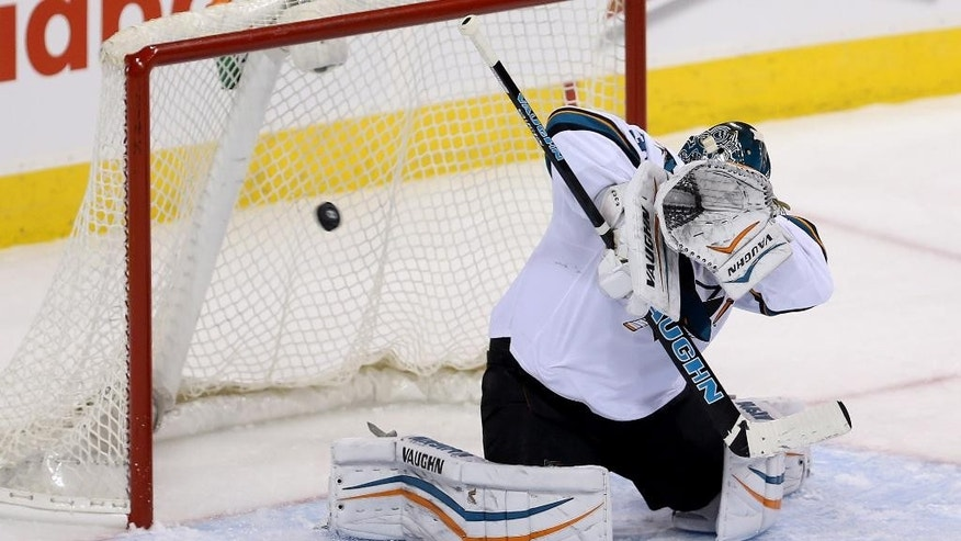 San Jose Sharks' goaltender Antti Niemi fails to block the puck as Winnipeg Jets Andrew Ladd scores during first period NHL hockey action in Winnipeg, Manitoba, Tuesday, March 17, 2015.  (AP Photo/The Canadian Press, Trevor Hagan)