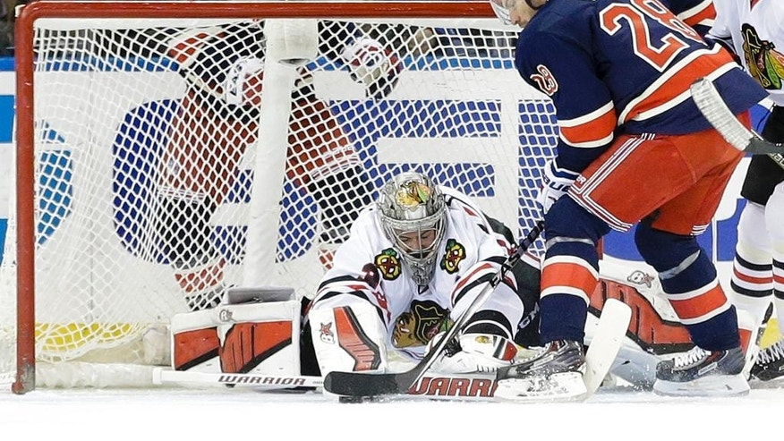 Chicago Blackhawks goalie Scott Darling stops a shot on the goal by New York Rangers' Dominic Moore (28) during the first period of an NHL hockey game Wednesday, March 18, 2015, in New York. (AP Photo/Frank Franklin II)