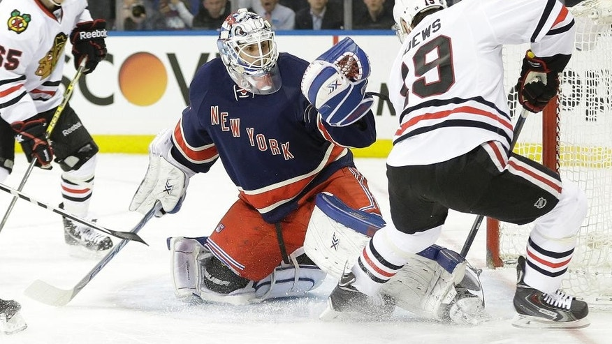 New York Rangers goalie Cam Talbot (33) stops a shot on the goal by Chicago Blackhawks' Jonathan Toews (19) during the first period of an NHL hockey game Wednesday, March 18, 2015, in New York. (AP Photo/Frank Franklin II)