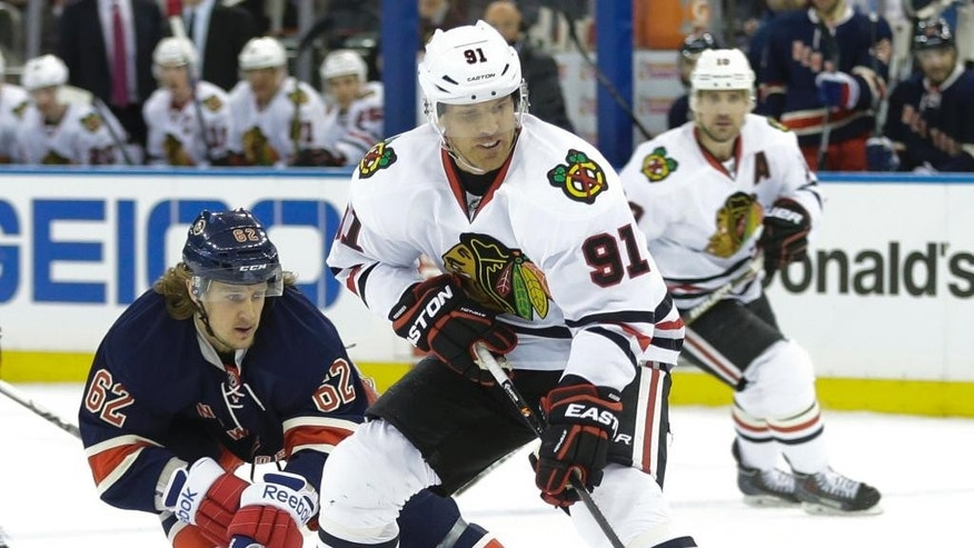 New York Rangers' Carl Hagelin (62) attempts to get control of the puck from Chicago Blackhawks' Brad Richards (91) during the first period of an NHL hockey game Wednesday, March 18, 2015, in New York. (AP Photo/Frank Franklin II)