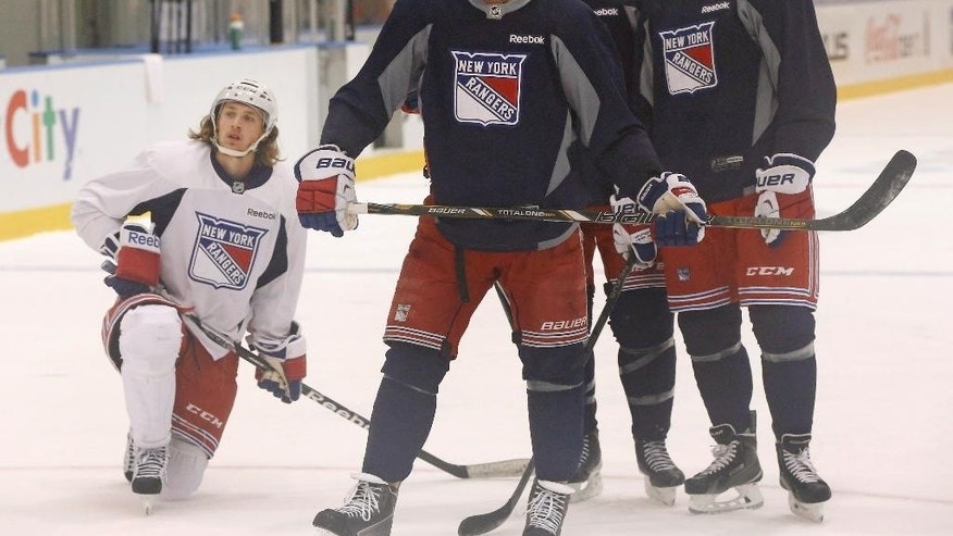 FILE - In this June 1, 2014 file photo, members of the New York Rangers, including Carl Hagelin, Ryan McDonagh, Dan Girardi and Chris Kreider pause during a morning practice at the team's training facility in Greenburgh, N.Y., while preparing for the Stanley Cup Finals. Sleep studies suggest that early morning workout hours before a game may not be ideal. (AP Photo/Kathy Willens)