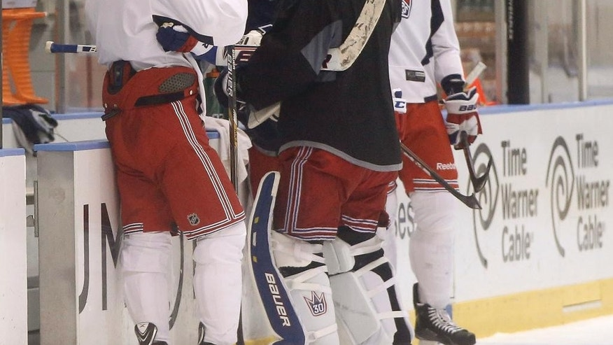 In this June 1, 2014 file photo, New York Rangers' Brain Boyle, far right, takes a drink as Daniel Carcillo clowns around with teammates during a break in a morning practice at the Rangers training facility in Greenburgh, N.Y., as the team is preparing for the Stanley Cup Finals. Sleep studies suggest that early morning workout hours before a game may not be ideal. (AP Photo/Kathy Willens)