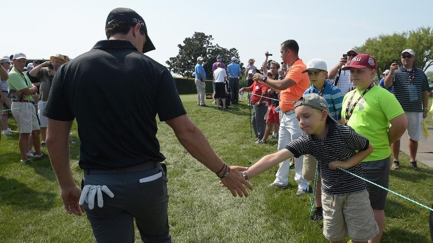 Rory McIlroy, left, of Northern Ireland, slaps hands with a young fan, while walking to the ninth tee, during the pro-am at the Arnold Palmer Invitational golf tournament in Orlando, Fla., Wednesday, March 18, 2015.(AP Photo/Phelan M. Ebenhack)