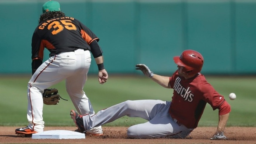 Arizona Diamondbacks' A.J. Pollock, right, slides safe behind San Francisco Giants' Brandon Crawford (35) with a double in the first inning of a spring training exhibition baseball game Tuesday, March 17, 2015, in Scottsdale, Ariz. (AP Photo/Ben Margot)