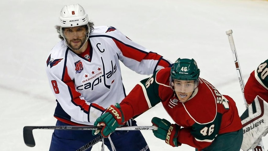 Minnesota Wild's Jared Spurgeon,right, keeps Washington Capitals' Alex Ovechkin of Russia occupied near the net in the first period of an NHL hockey game, Thursday, March 19, 2015, in St. Paul, Minn. (AP Photo/Jim Mone)