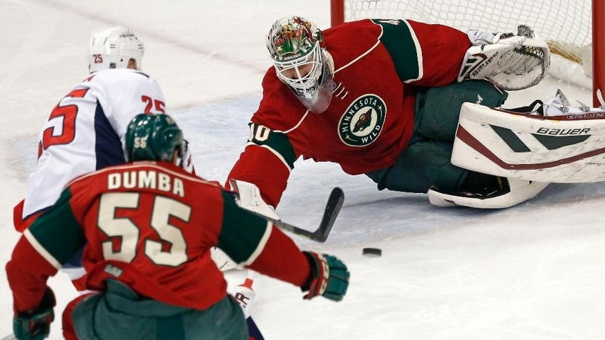 Minnesota Wild goalie Devan Dubnyk, right, dives to stop a shot by Washington Capitals' Jason Chimera, left, in the first period of an NHL hockey game, Thursday, March 19, 2015, in St. Paul, Minn. Also defending is Wild's Matt Dumba (55). (AP Photo/Jim Mone)