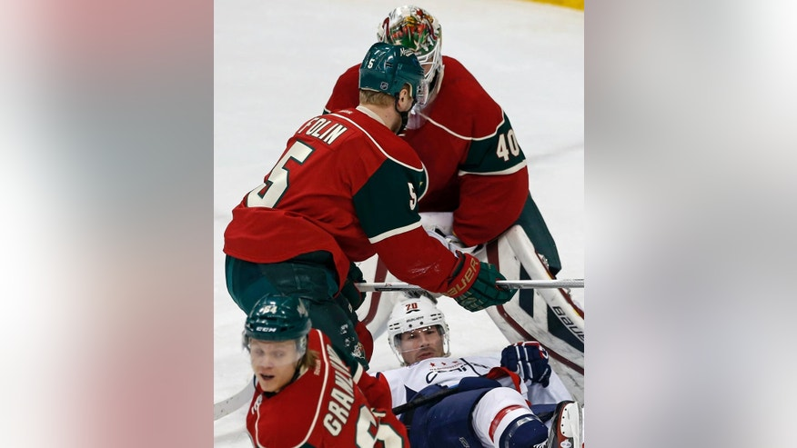Washington Capitals' Troy Brouwer  bottom, hits the ice after he was squeezed out between Minnesota Wild's Christian Folin, top left, of Sweden, and goalie Devan Dubnyk in the first period of an NHL hockey game, Thursday, March 19, 2015, in St. Paul, Minn. (AP Photo/Jim Mone)