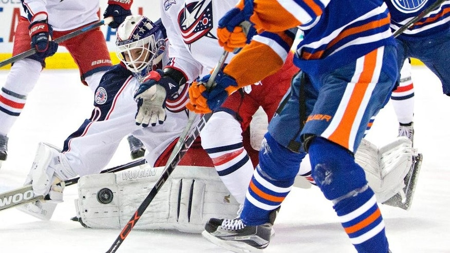 Columbus Blue Jackets goalie Curtis McElhinney (30) makes a save against the Edmonton Oilers during second period NHL hockey action in Edmonton, Canada on Wednesday March 18, 2015. (AP Photo/The Canadian Press, Jason Franson)